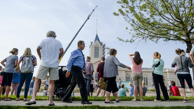 A crowd gathers to watch as a golden statue of the Angel Moroni is placed on top of the Temple of the Church of Jesus of Latter-day Saints on Wednesday in Fort Collins.