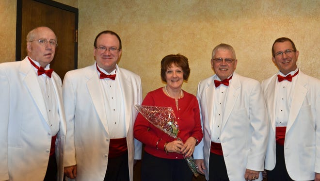 Pictured, from left, are Clipper City Chordsmen Bruce Beyer, Anthony Schreiter, message recipient Susan Henderson, Jim Rasmus and Don Lewellen. The Chordsmen delivered messages of love on Valentines Day with a song, a rose and a personalized card. A digital photo was also taken to remember the event.
