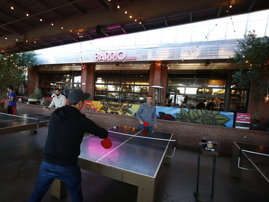 Winston Duong (L) and Josh Albers play ping pong at
