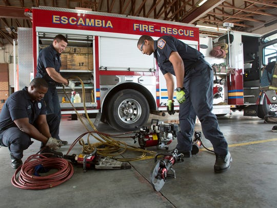From left, Escambia County firefighters Otis Evans, Kevin Chacin and Terrell Jackson perform a mandatory daily systems check on a piece of equipment at fire station No. 17 on May 10, 2016.