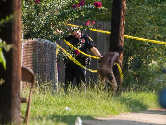 Police get help with the crime tape as they work the scene on Rosa Parks near Burgwyn Montgomery, Ala., on Tuesday September 5, 2017.
