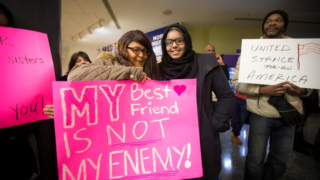 """Sunday, Jan. 29, 2017: Lynette Johnson, 18, left, of Lakeside Park, Ky., stands with her friend Khadeja Ahmedou, 16, of Ft. Mitchell, Ky. during a demonstration at CVG Airport in Hebron, Ky., to protest against President Donald Trump's recent executive order on travel and immigration for Muslims. Khadeja, who is Muslim, was talked into coming to the protest by her best friend, Lynette, who is Christian. Lynette made a sign that read, """"My best friend is not my enemy."""" They are both students at Dixie Heights High School."""