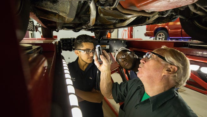 Jose Salazar, Jay Dollard and automotive instructor Jack Malloy perform a pre-alignment inspection of the suspension in an auto bay at Delaware Technical Community College's Stanton campus.