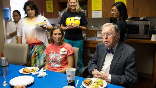 Eighty-sevein-year-old Dr. George Flood says grace during his retirement lunch in Driscoll Children's Hospital's developmental pediatric medicine department on Wednesday, May 10, 2017. It was his last day of work.