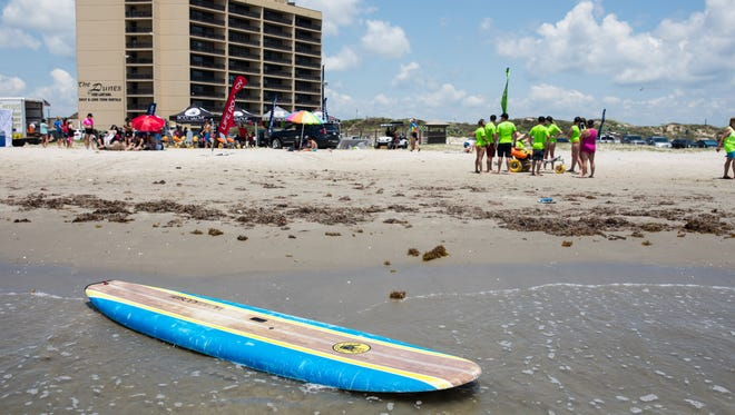 """A surfboard sits in the surf during """"They Will Surf Again"""" event at Horace Caldwell Pier in Port Aransas on Saturday, June 10, 2017."""