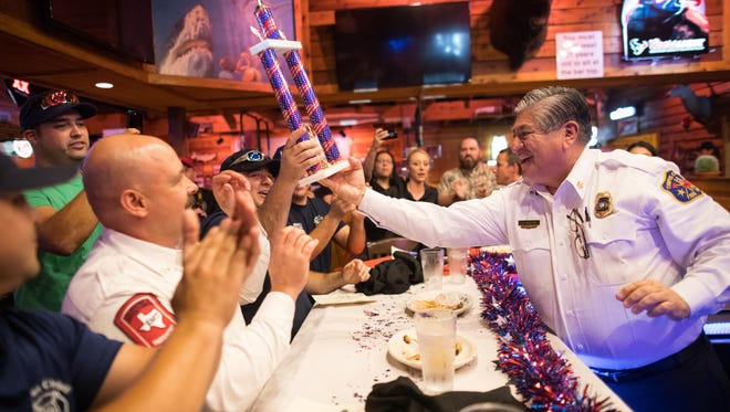 Fire Chief Robert Rocha hands the fire department team the trophy after winning the annual Police, Fire and media rib eating contest kicking off Tip A Cop and Firefighter Night at Texas Roadhouse on Tuesday, June 27, 2017.