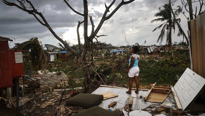 Puerto Rican woman stands amid the ruins of her home.