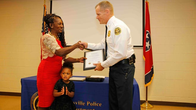 Police Chief Al Ansley congratulates Clarksville Police Sgt. Cheryl Anderson, who is retiring after 30 years with the department.