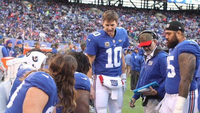 New York Giants quarterback Eli Manning talks to his offensive linemen as they sit on the bench in the second half.