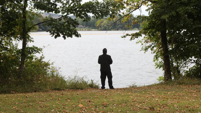 Jefferson LaSala looks out over Pompton Lake. He was a long time resident of Pompton Lakes before recently moving away. His mother and brother suffered severe neurological illnesses he says is because of the pollution from Dupont. Chris Pedota / The Record