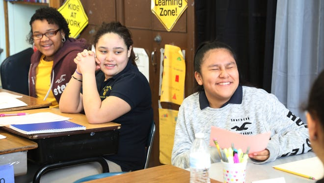 Emely Nunez and Jolie DeJesus watch as Valerie Garcia has a laugh with her fellow seventh grade students during Saturday morning class.