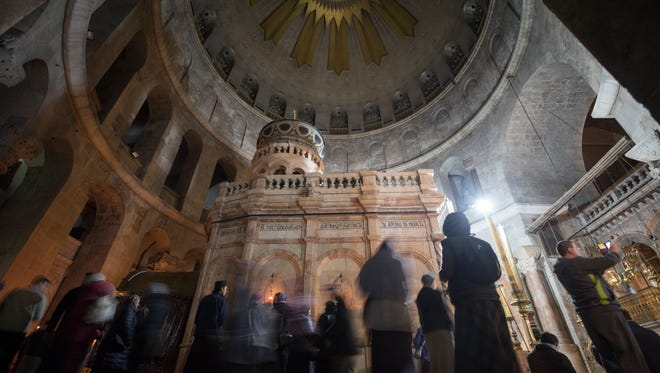 Christian devotees pray at the Church of the Holy Sepulchre in Jerusalem's old city as it reopens after three days of closure by the heads of the Christian Churches leaders in protest against Israeli tax measures, on Feb. 28, 2018.