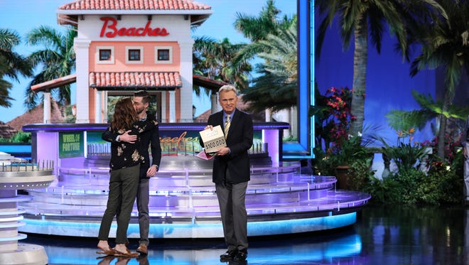 """Karly and Aaron Mandell embrace as """"Wheel of Fortune"""" host Pat Sajak presents them the prize for the bonus puzzle, $100,000."""