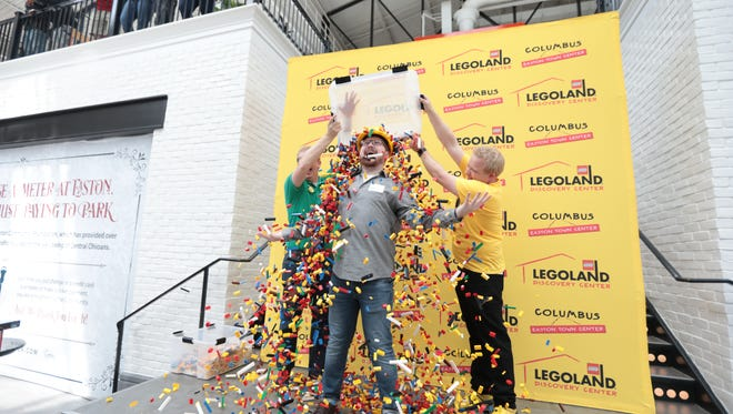 Maxx Davidson gets Legos dumped on him after winning a competition Sunday at Easton Town Center to become the master builder of the new Legoland Discovery Center, which opens Sept. 21