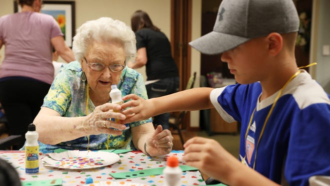 Seth Knott, 12, helps Jean Ledford with a paint marker during the Timeless Wings of Learning program at Brookdale Senior Living on Monday. Youngsters from North Terrace Church of Christ visited the facility to visit with their grandfriends.