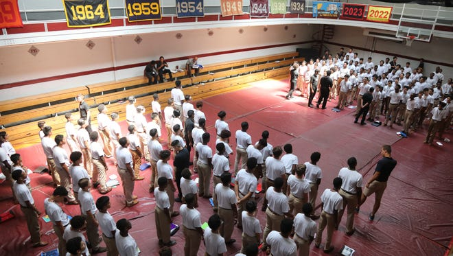 The St. Benedict's freshman chant school mottos and sing school songs in the school gym as part of their indoctrination process the school puts them through to become members of the St. Benedict community.
