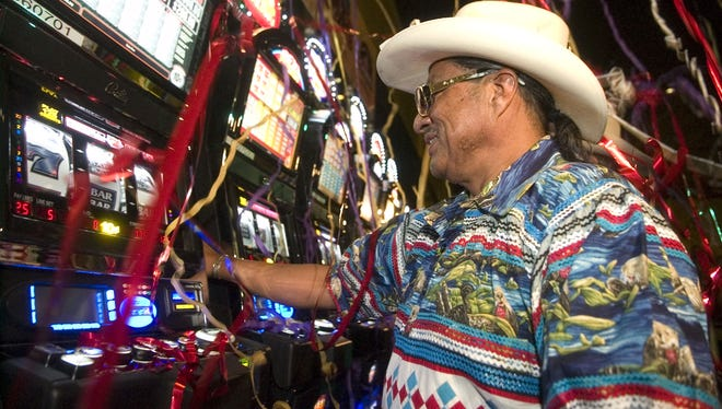 """As strings of confetti fall around him, Mitchell Cypress, chairman of the Seminole Tribe of Florida Tribal Council, ceremonially participates in the """"first pull"""" on one of the new recently installed Vegas Style slot machines at the Seminole Casino in Immokalee, Fla., on June 12, 2008."""