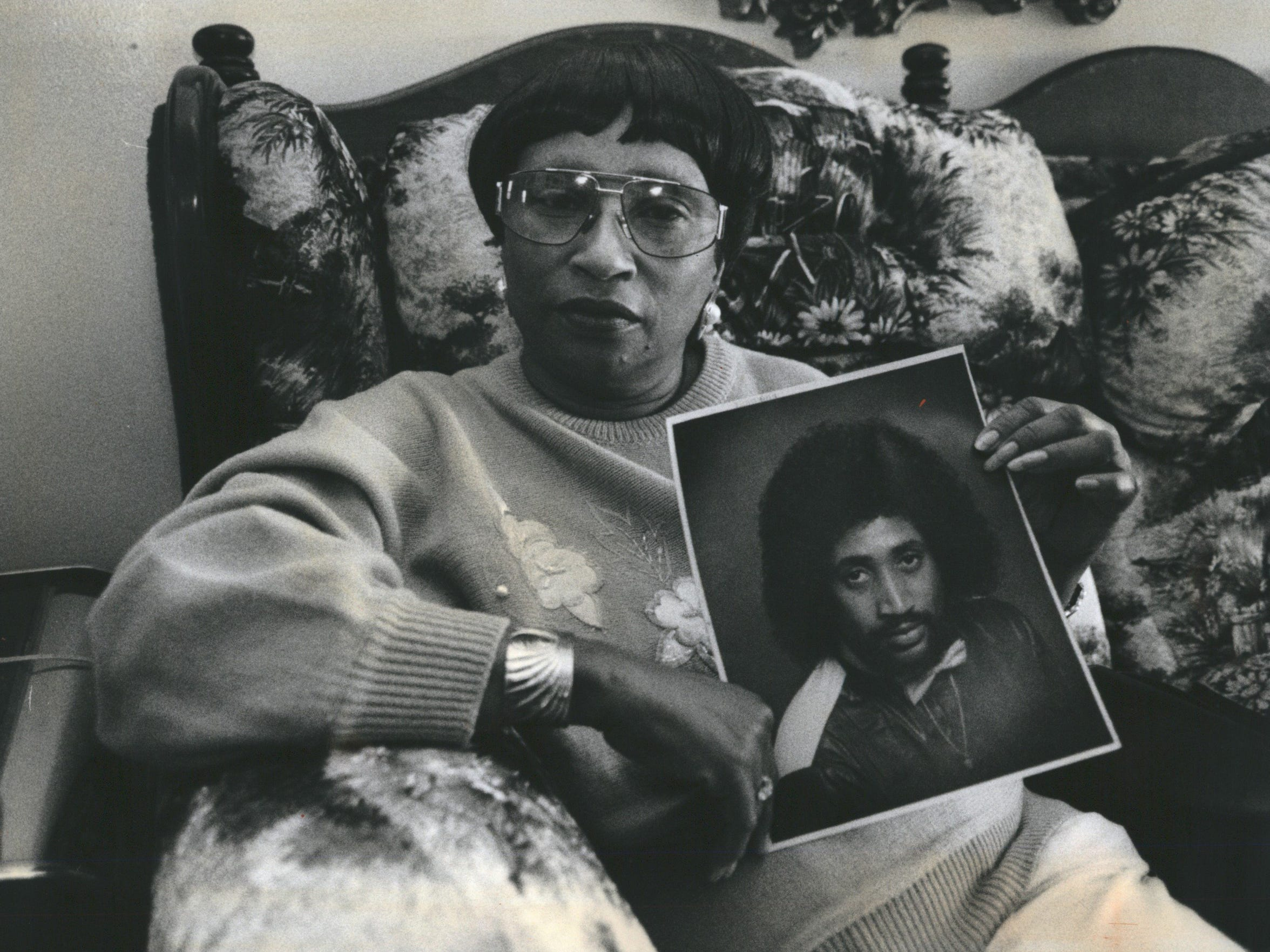 A November 6,1992, photo shows Patricia Ann Green, 52, of Detroit, as she holds a picture of Malice Wayne Green, her son. Malice died in Detroit, after police beat him.