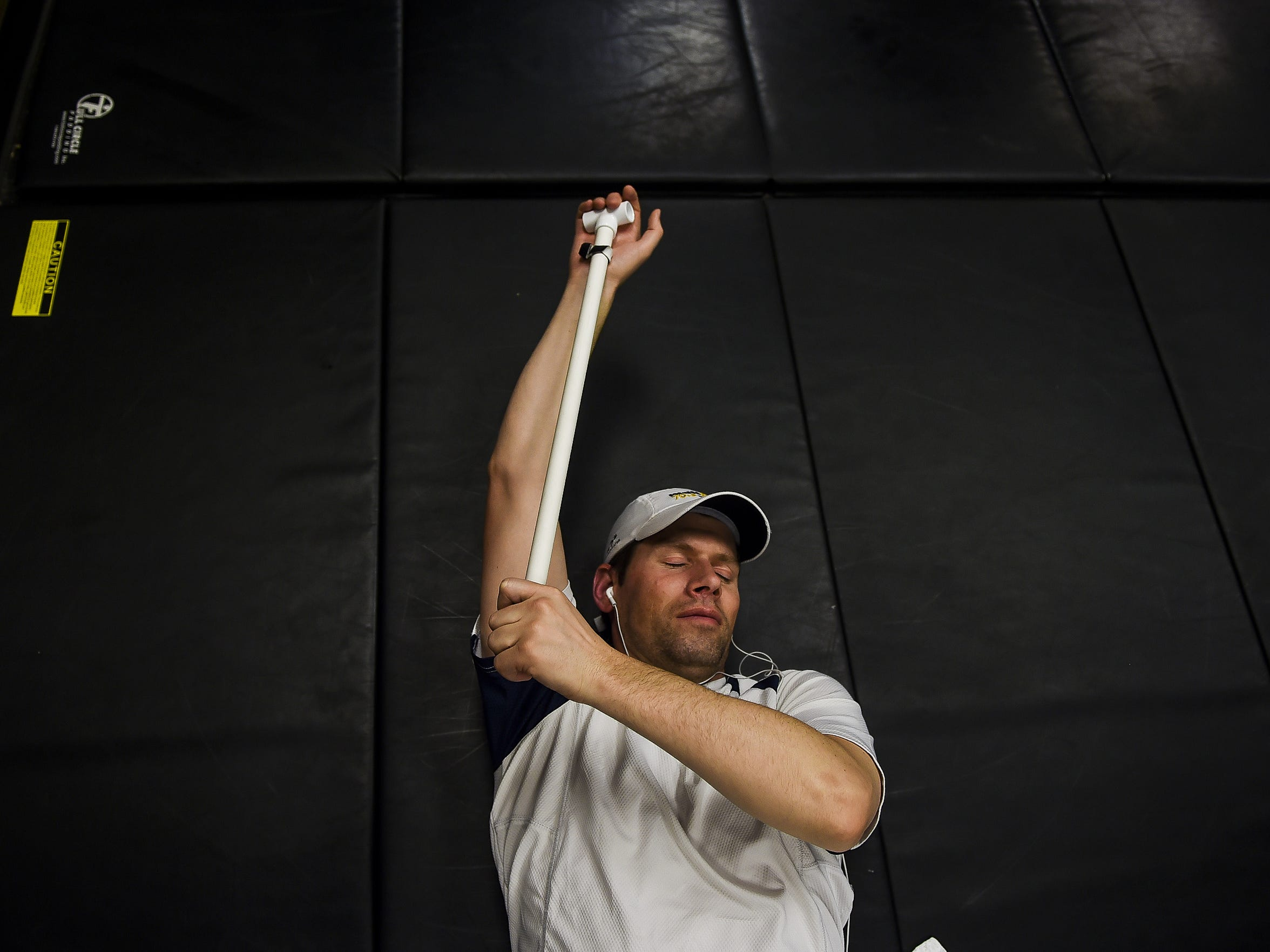 Jeff Wicks uses a PVC pipe to help stretch his shoulder