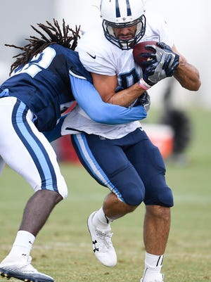 Titans tight end Jace Amaro (88) is hit by safety Denzel Johnson (42) as he pulls in a catch during training camp practice at Saint Thomas Sports Park on Thursday, Aug. 10, 2017.