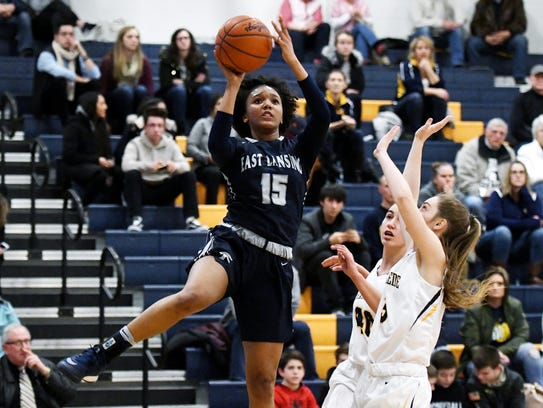 East Lansing's Jaida Hampton, left, scores on a layup