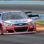 AJ Allmendinger waits by his car before his qualifying run for Sunday's NASCAR Sprint Cup race at Watkins Glen International.