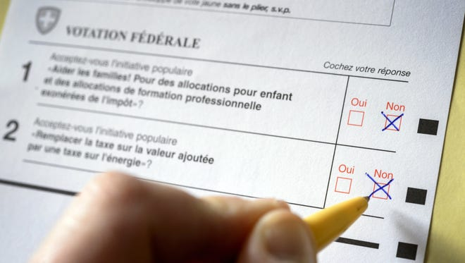 A man crosses a box on a ballot paper in Lausanne  as two popular initiatives, a tax exemption for family allowances and an energy tax were rejected by Swiss citizens on March 8, 2015.