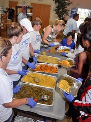 Volunteers form an assembly line to prepare family-sized Thanksgiving dinners during the Feeding of the 5,000 outreach at Lamb of God Church Nov. 23.