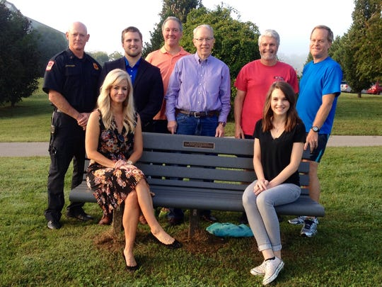 Doug Campbell's family and friends sit on a bench with his name near the site where he went into cardiac arrest earlier this year. Standing, from left: Mike McCutcheon, Dane Daniels, Todd Gregory, Kent Fourman, Tommy Allen and Joe Trammell. Seated, from left: Joy Campbell and MacKenzie Campbell.