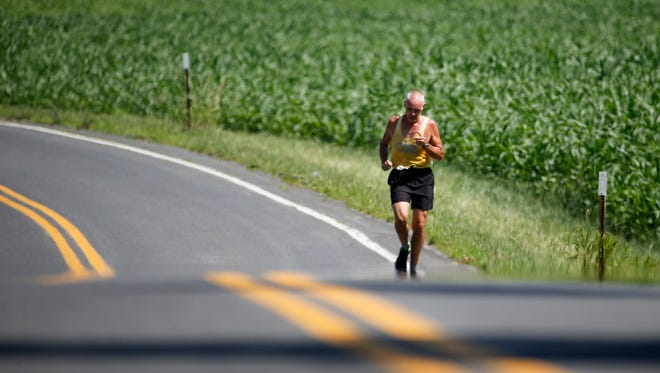 Ray Framarin, a member of Kinderhook Runners Club, runs along County Route 21 on a hot summer morning on Wednesday, July 6, 2016, in Stuyvesant, N.Y.