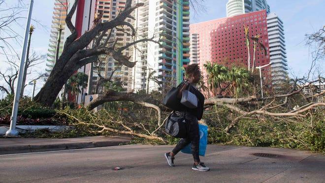 Estrella Palacios walks through debris caused by Hurricane Irma in Miami,  Sept. 11, 2017.
