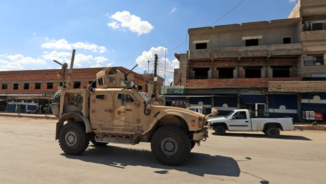 Vehicles from the U.S.-led coalition battling the Islamic State patrol the town of Rmelane in Syria's Hasakeh province on June 5, 2018.
