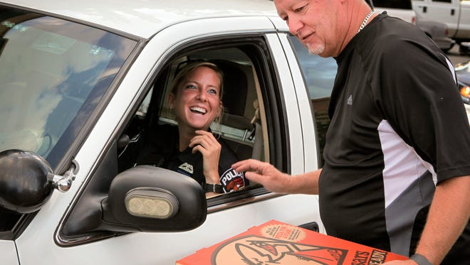 Murfreesboro Police Officer Jessica Rice receives pizza from Shaun Murphy, a retired firefighter and event supporter.