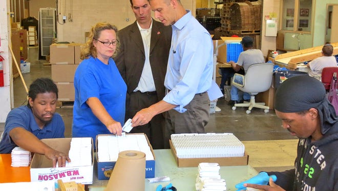 In this 2014 file photo, ForSight Vision's production manager Michelle Shenberger talks to Rep. Scott Perry, right, and his deputy chief of staff Bob Reilly, center, about how ForSight's vision-impaired employees are reformatting books-on-tape for the Library of Congress.