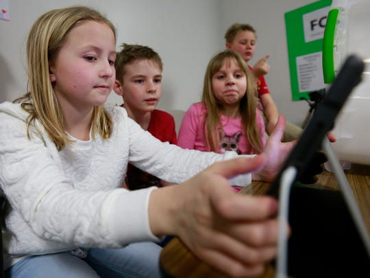 Fourth-graders Elin Nielsen, left, Shiloh Burgess, and Mira Patterson set up an iPad to record their podcast March 6, 2017, at Riverside Elementary School in Ringle.