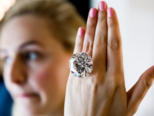 Photo shows a model displaying a 110.92 carat round