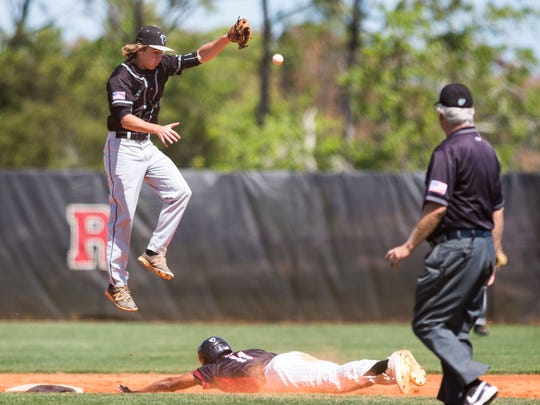 Jensen Beach's Kyle Abbott (top) leaps for the ball as Port St. Lucie's Harry Vargas steals second base — and later scores on a hit by Ziggy Thomas — during the second inning of the high school baseball game Tuesday, March 13, 2018, at Port St. Lucie High School.