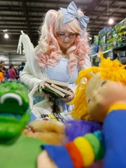 Brianna Ryscuck of Middletown peruses manga books while dressed in Lolita fashion during the Galactic Con in Middletown Saturday.