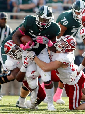 Michigan State's LJ Scott, center, is stopped by Indiana's Nathanael Snyder, left, and Chase Dutra, right, during the second quarter of an NCAA college football game, Saturday, Oct. 21, 2017, in East Lansing, Mich.