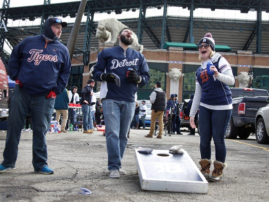 Jordan West, 28, of Sterling Heights, left, looks on as his brother Devan West, 30, of Sterling Heights celebrates a small victory as Shannon Barrington, 24, of Sterling Heights makes her corn hole toss before the Detroit Tigers face the Boston Red Sox on Opening Day on Friday April 7, 2017, at Comerica Park in Detroit.