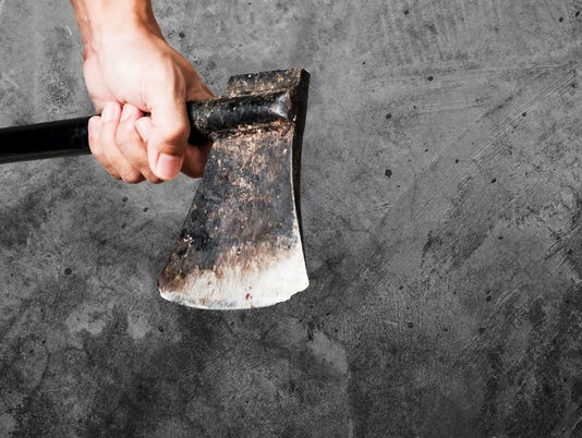 Man holding old rusty axe, on concrete background