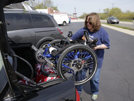 The Bellin Health Stroke Support Group is helping participants adapt to riding special recumbent bikes to aid in their recovery.  Stroke survivor Michelle Nelson of Little Suamico takes her new folding bike out of her trunk for a ride along the Fox River Trail on Monday, May 9, 2016.