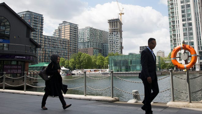 Pedestrians walk past the Lincoln Plaza residential apartment building complex in the Canary Wharf business, financial and shopping district in London, on May 21, 2015. Developers are seeking to appeal to foreign buyers, who favor apartments, with high-rise, high-volume projects, particularly in east London.