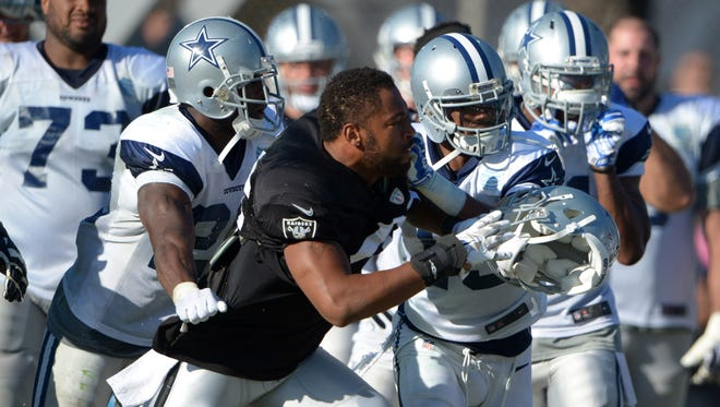 Oakland Raiders linebacker Justin Cole (46) is restrained by Dallas Cowboys players at scrimmage at River Ridge Fields.