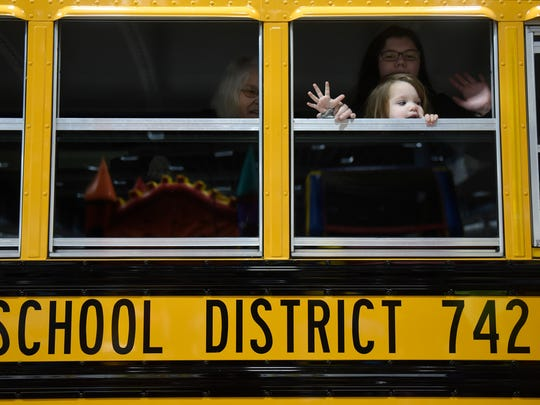 Maddy Riedman-Lenarz and Emma Krey wave to the crowd while touring a school bus during the education expo at the River's Edge Convention Center in St. Cloud in January 2017.