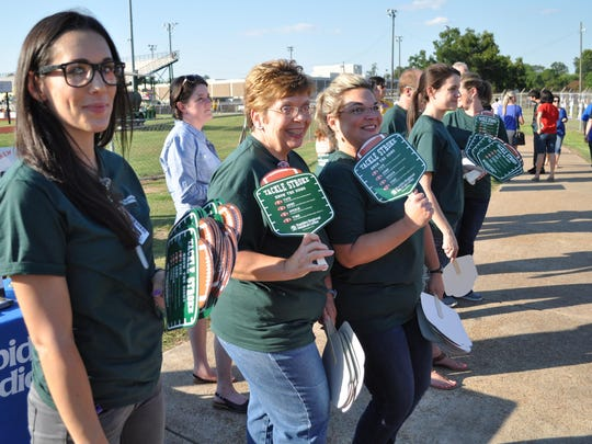 Rapides Regional Medical Center volunteers hand out fans Friday during the football jamboree at Alexandria Senior High School.