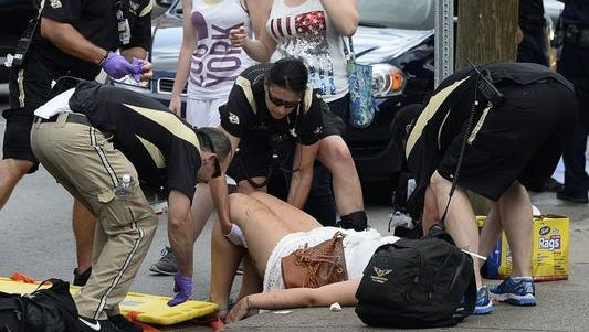 Vanderbilt Life Flight Event Medicine personnel give medical aid to a woman they say fainted from heat exhaustion along Second Avenue South during the CMA Music Festival on Saturday.