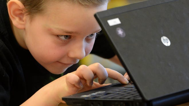 Colton Selby uses a netbook for research during a reading assignment Thursday in Cassandra Butry's second-grade class at Nicolet Elementary School.