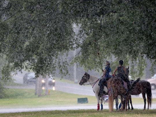 Sandy Hudson (left) and Brittany Hardy wait out a July downpour under a tree before the start of the Cordova Community Center's Annual Independence Day Celebration and Parade.