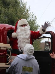 Santa arrives by antique fire truck at Mister Ed's